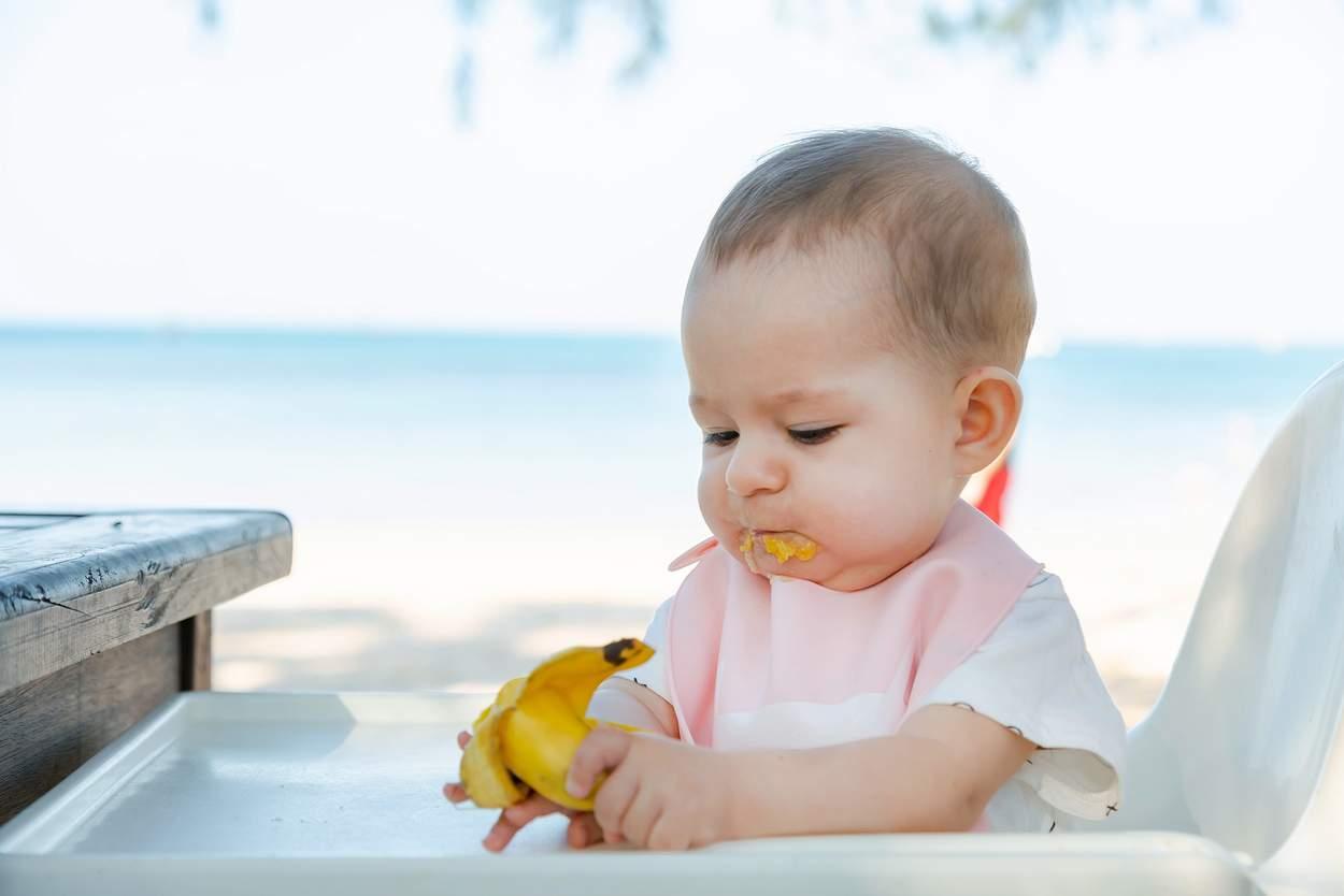 Baby isst Banane im Hochstuhl