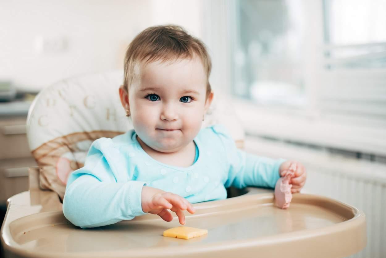 Baby isst Käse im Hochstuhl