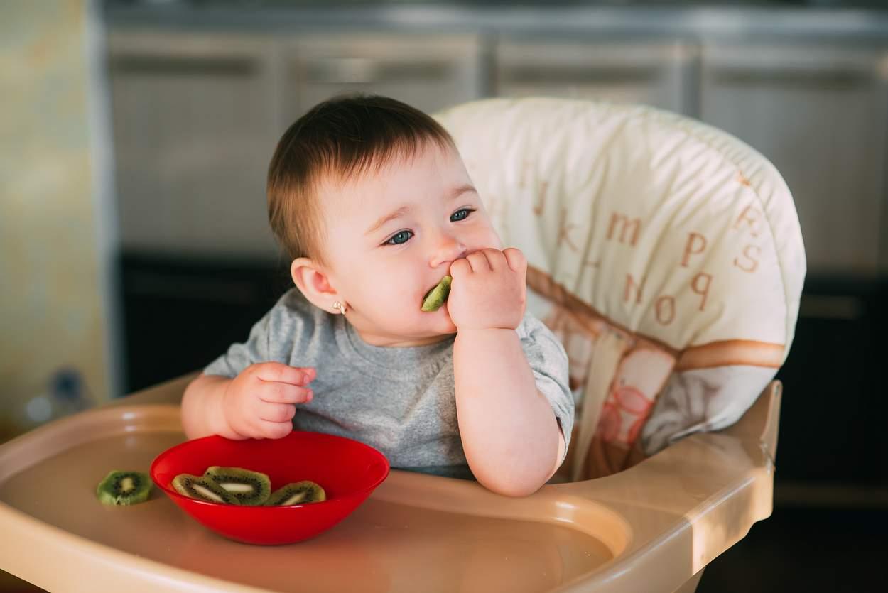 baby isst kiwi im hochstuhl