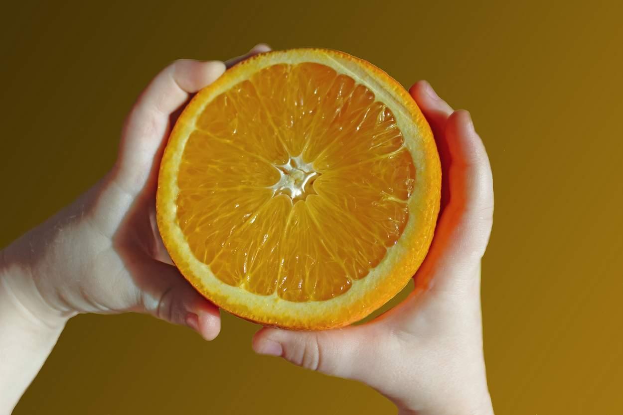 Babyhände halten aufgeschnittene Orange fest