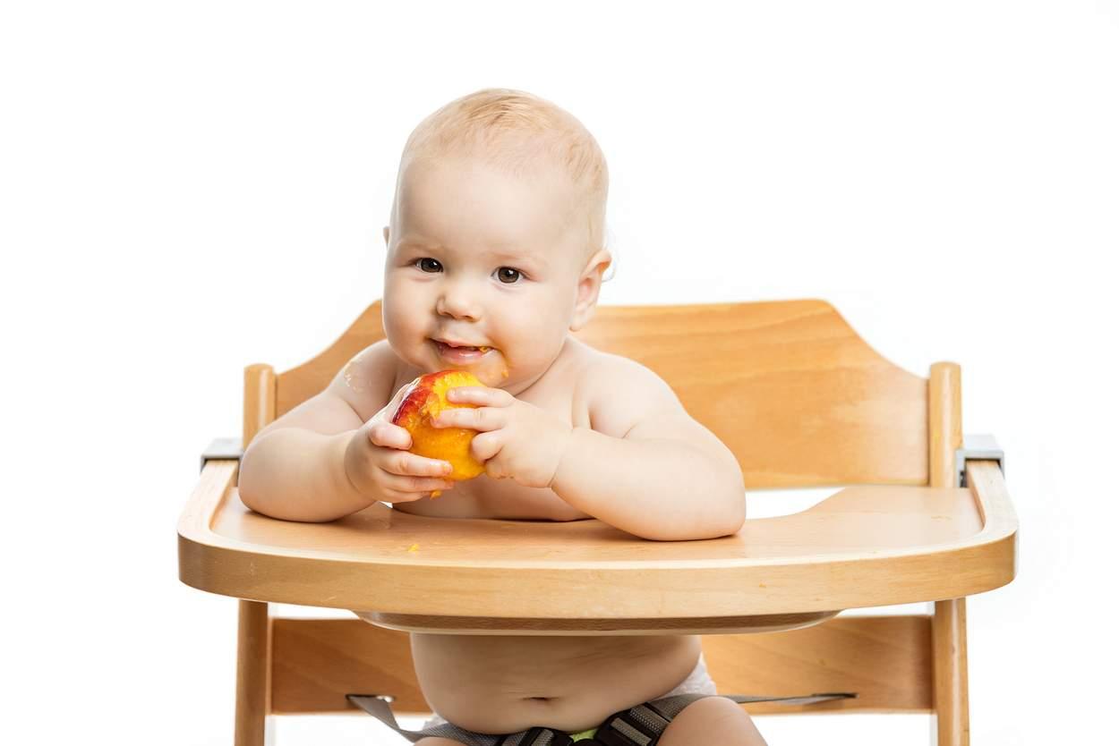 Baby sitzt im Hochstuhl und isst Pfirsich mit Hand