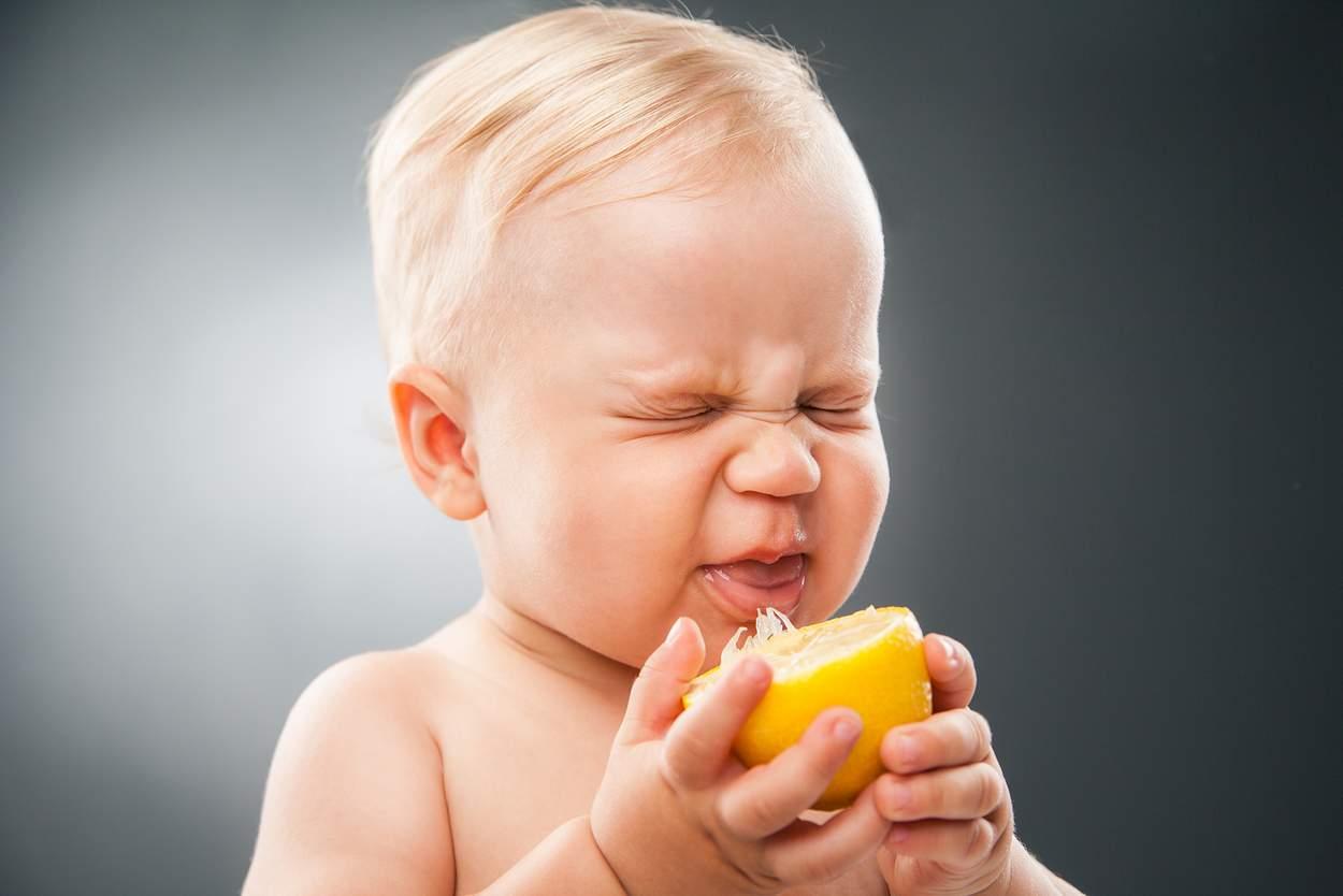 Baby beißt in Zitrone und verzieht das Gesicht