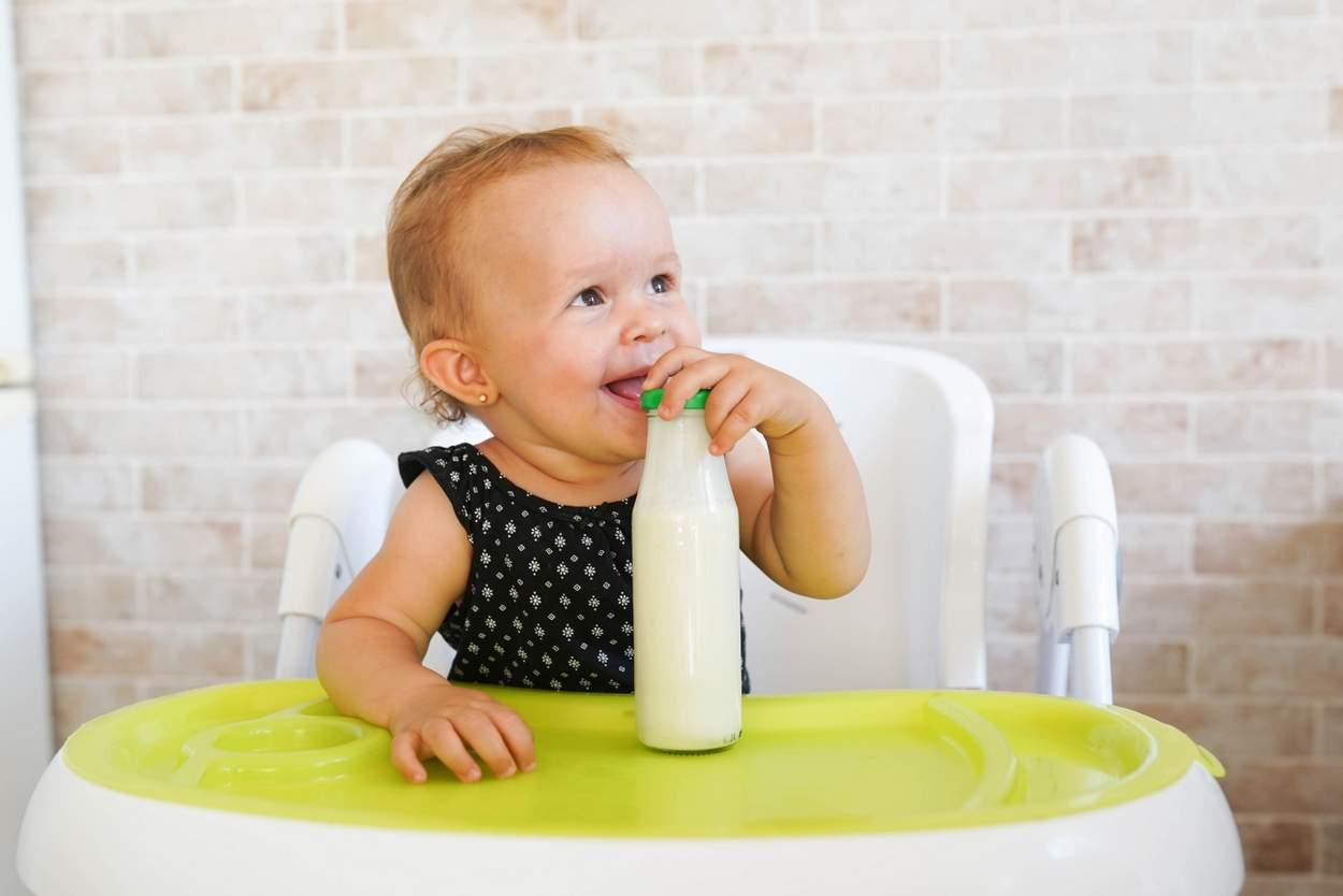 Baby sitzt mit Kefir am Tisch