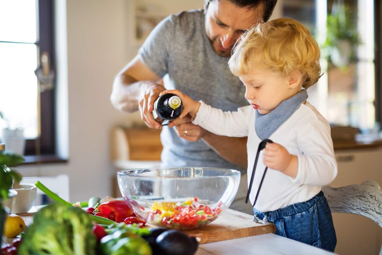 Baby kippt Olivenöl in Salatschüssel