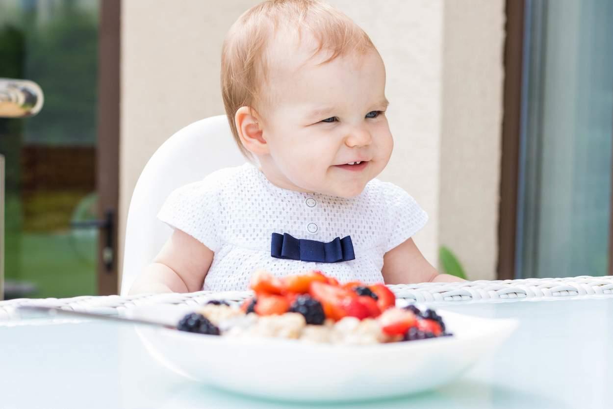 Baby isst Haferflocken im Müsli und Porridge