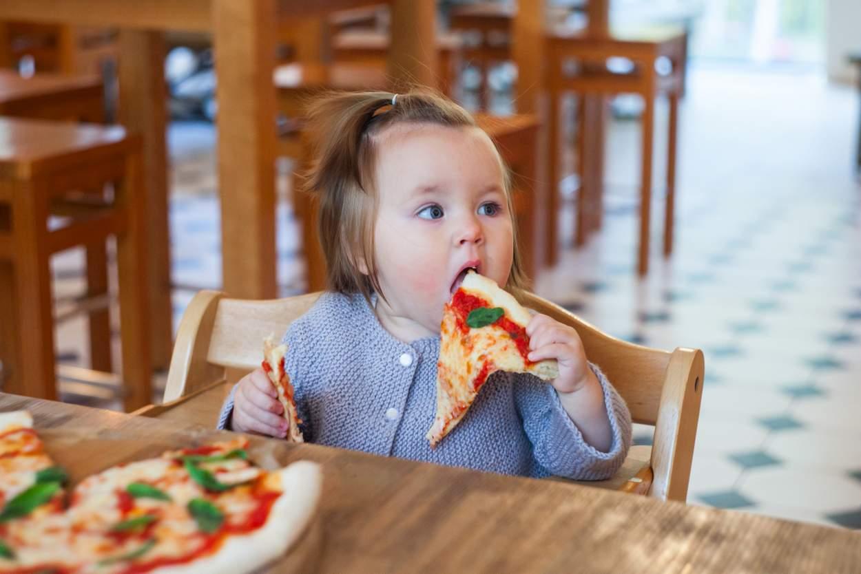 Baby isst salzige Pizza mit Hände