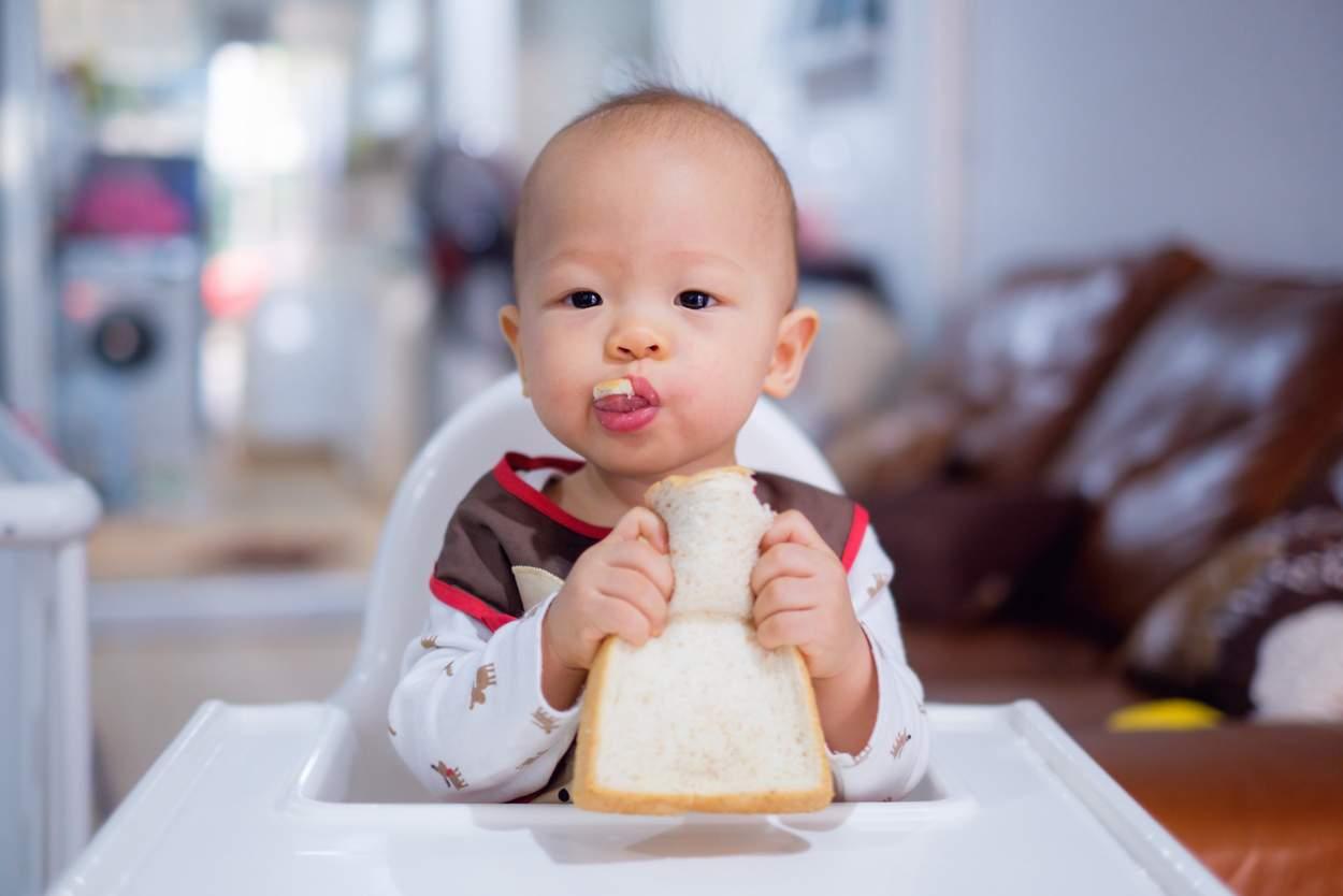 Baby isst Scheibe Toastbrot