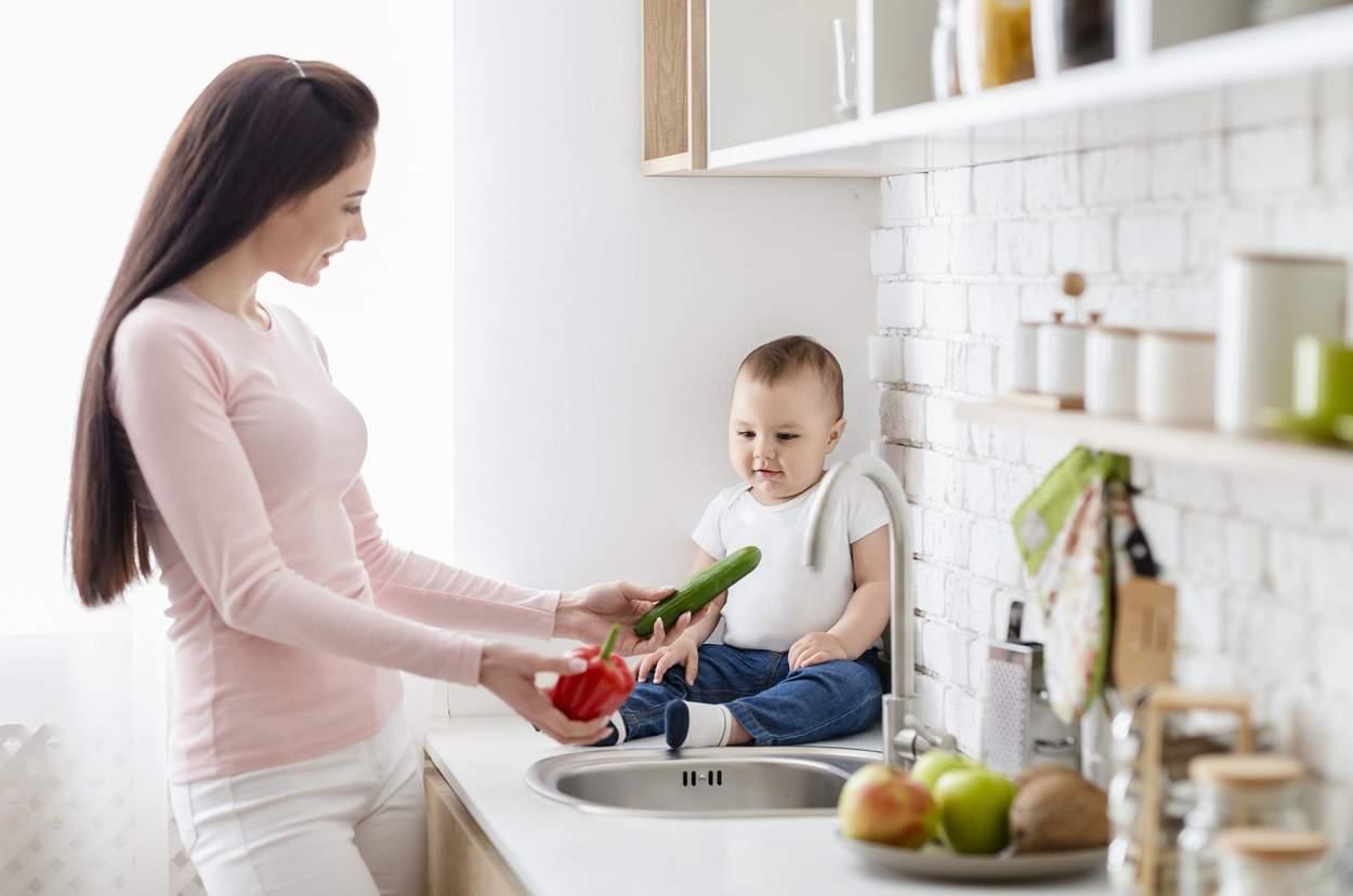 mutter-kocht-mit-kleinkind-auf-kuechenzeile