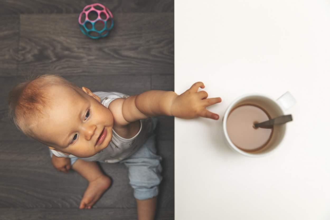 Baby greift zur Tasse mit Kakao