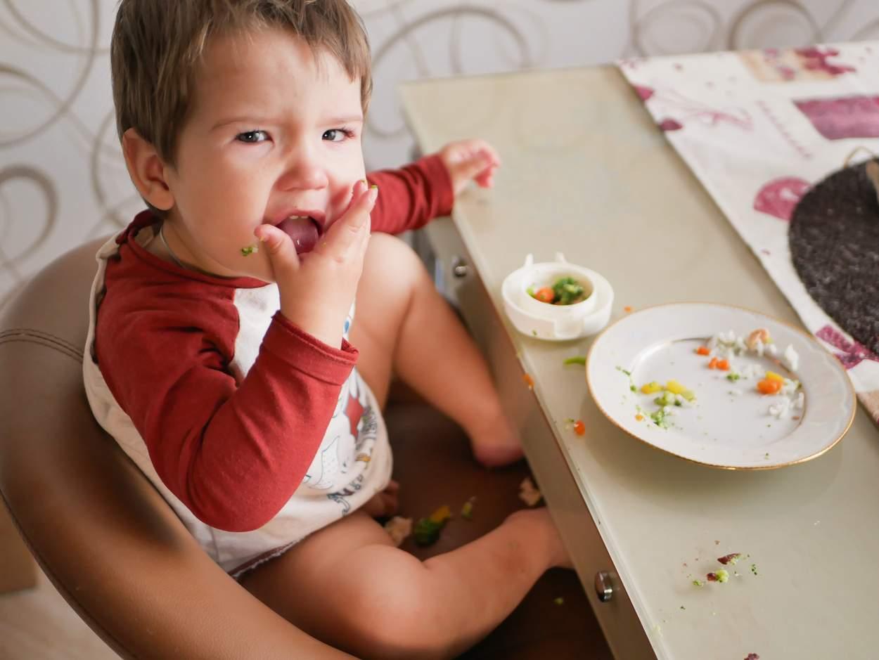 Kind isst Reis und Gemüse mit Hände