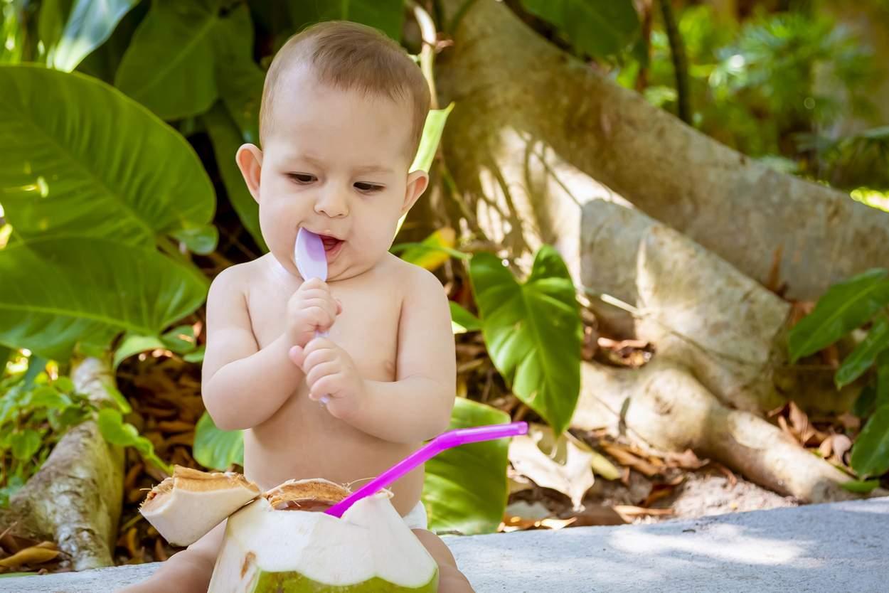 Baby mit Kokosnuss am Strand